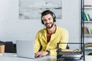 Smiling bearded businessman listening to music and looking at camera at office